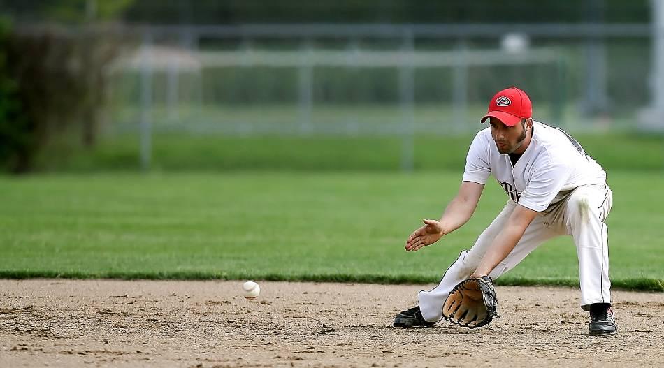 Baseball infielder bends down to field groundball.
