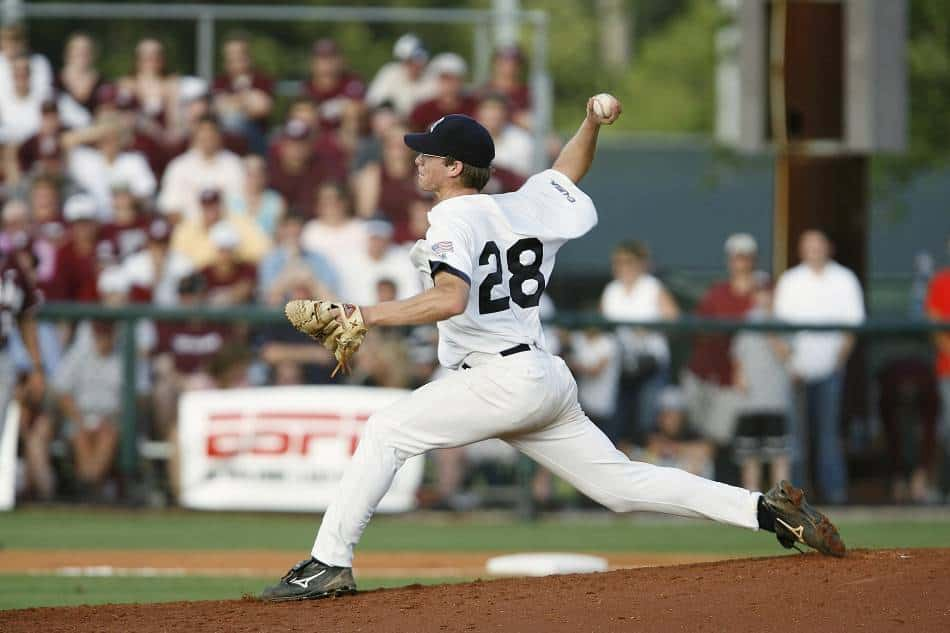 College baseball pitcher throws ball toward home plate.