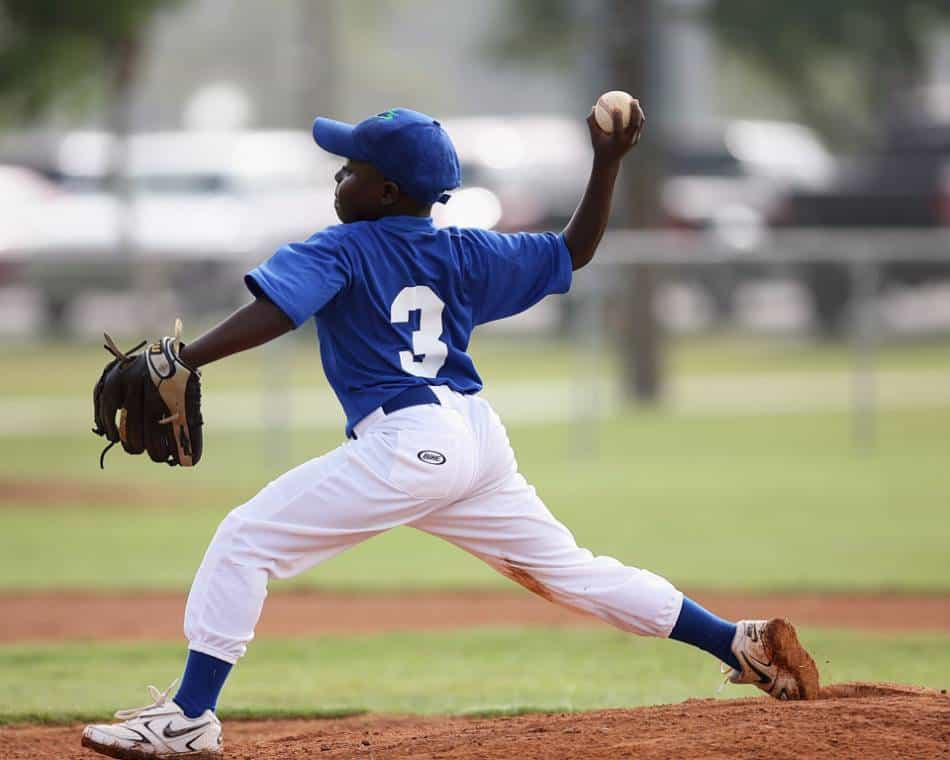 Young baseball pitcher in blue throws the ball home.