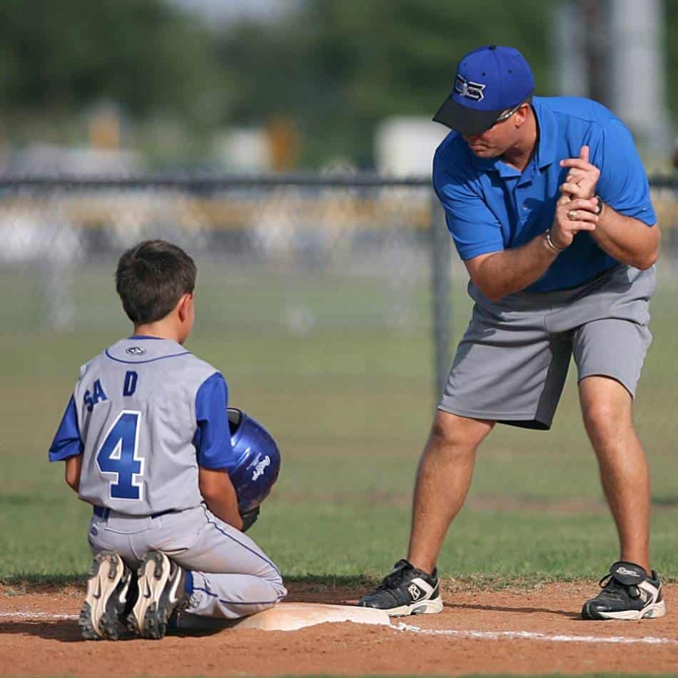 Youth baseball coach shows player proper batting stance.