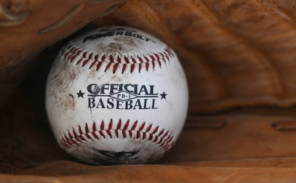 A baseball sitting in a baseball glove.