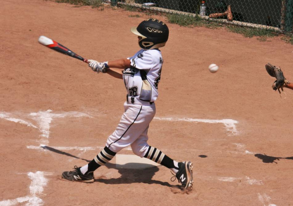 Youth baseball players swings and misses at a pitch.