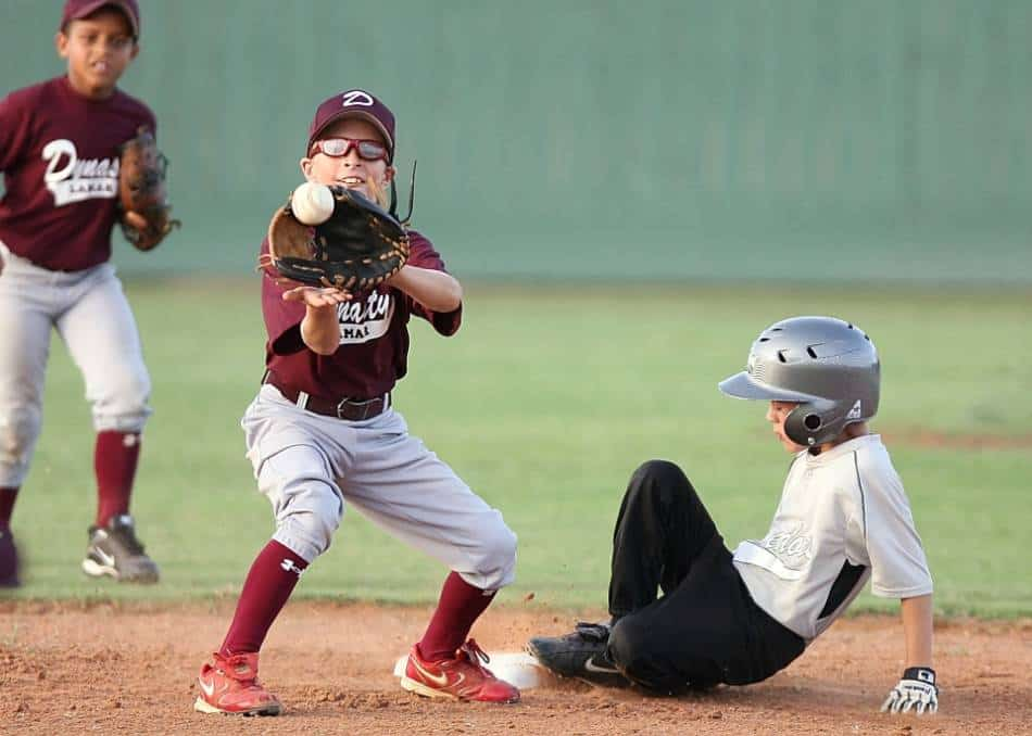 Youth baseball player prepares to catch the ball at second base, as a runner slides into the base.