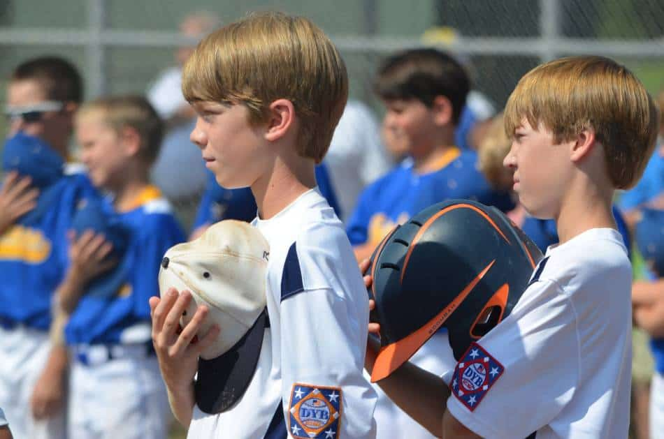 Youth baseball players take off their hats and helmets for the national anthem.