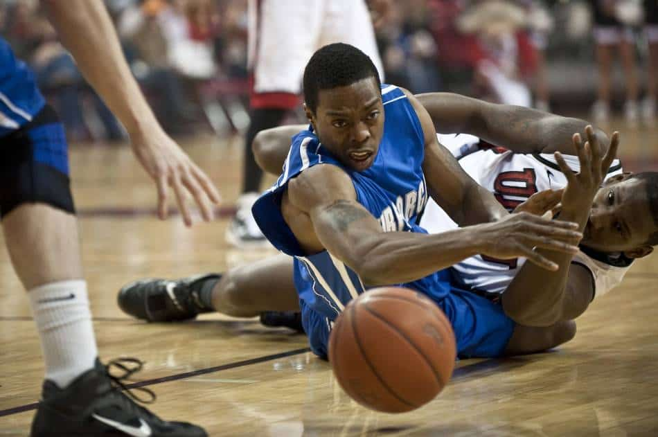 Basketball players dive for a loose ball.