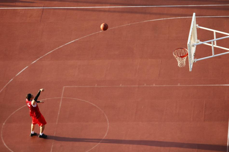 Basketball playing shooting free throws at park.