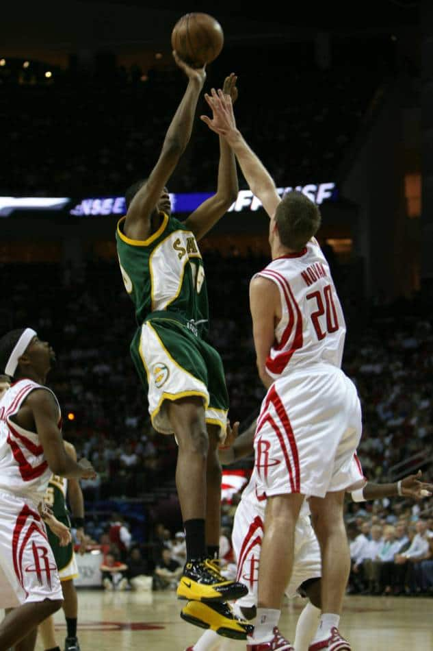 Professional basketball player shoots over defender.