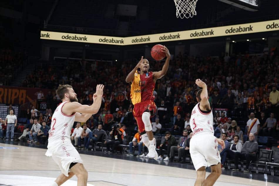 Male basketball lays up basketball.