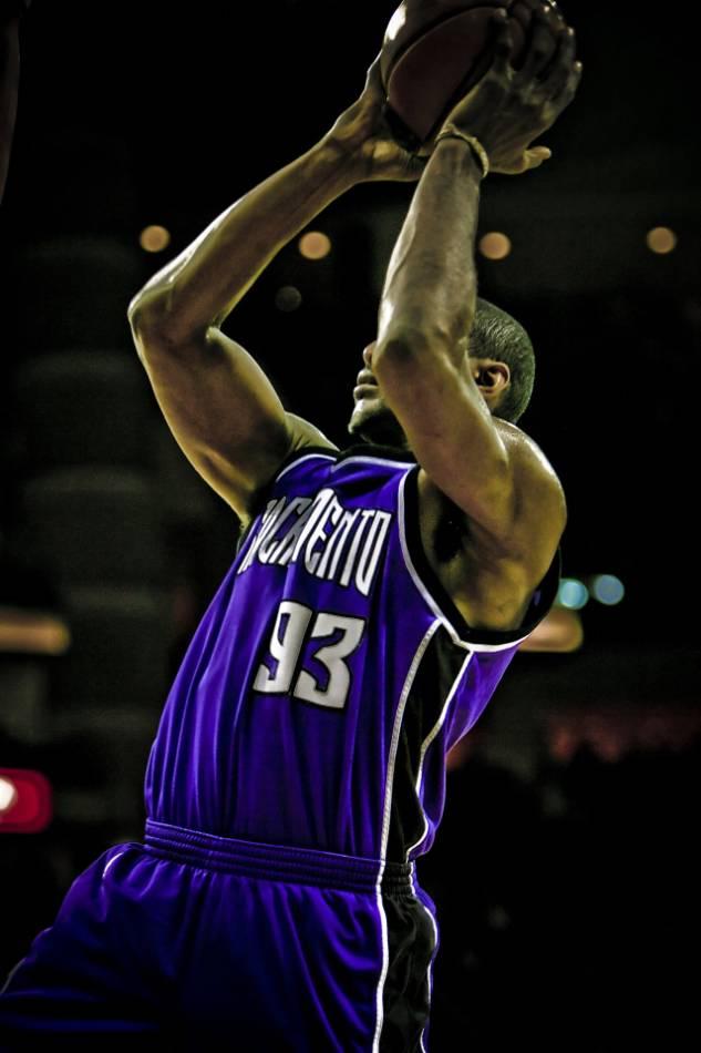 Professional basketball player shoots basketball.
