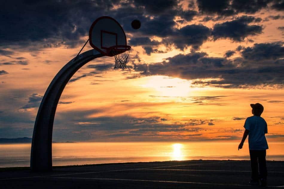 Boy shooting basketball as the sun sets.