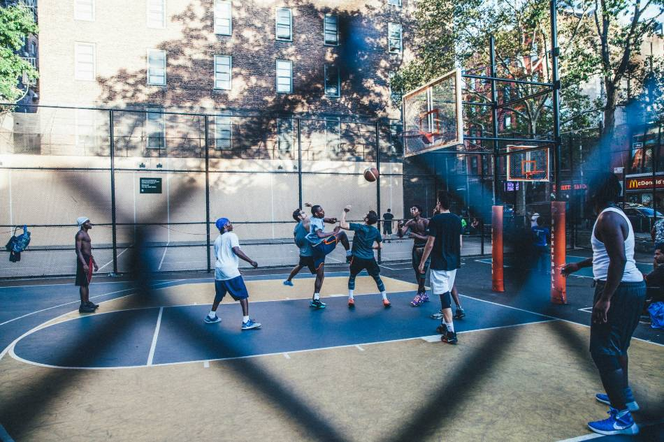 Group of men play basketball in park.