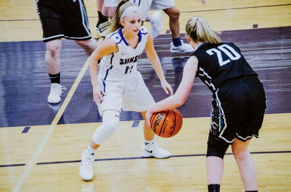 Female basketball player with ball decides her next move.