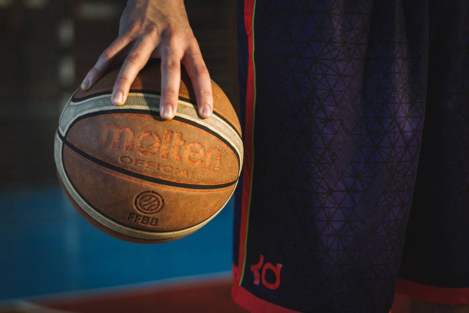 Man holds basketball with one hand.