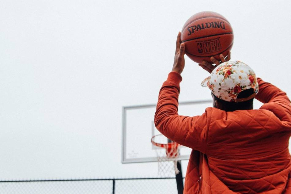 Man in hat and orange jacket shooting a basketball at the park.
