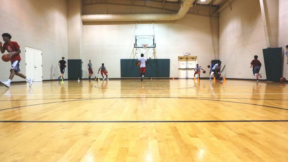 Basketball team going through dribbling drills inside a gym.