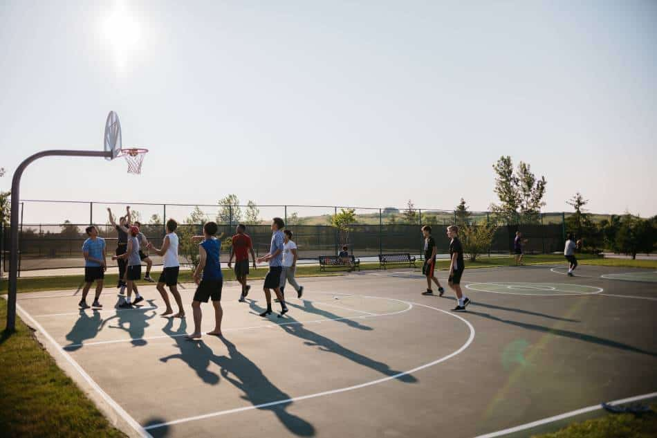 Group of boys playing half-court basketball at the park.