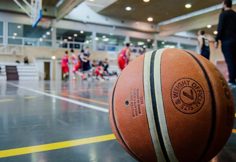 Basketball shown in the foreground with a game going on in the background.