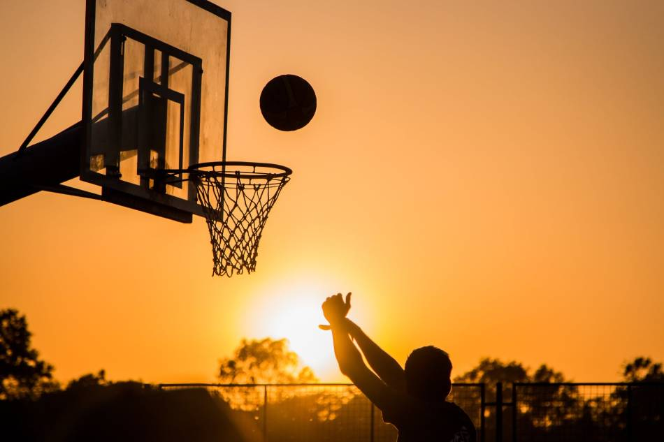 Person shooting baskets at sunset.