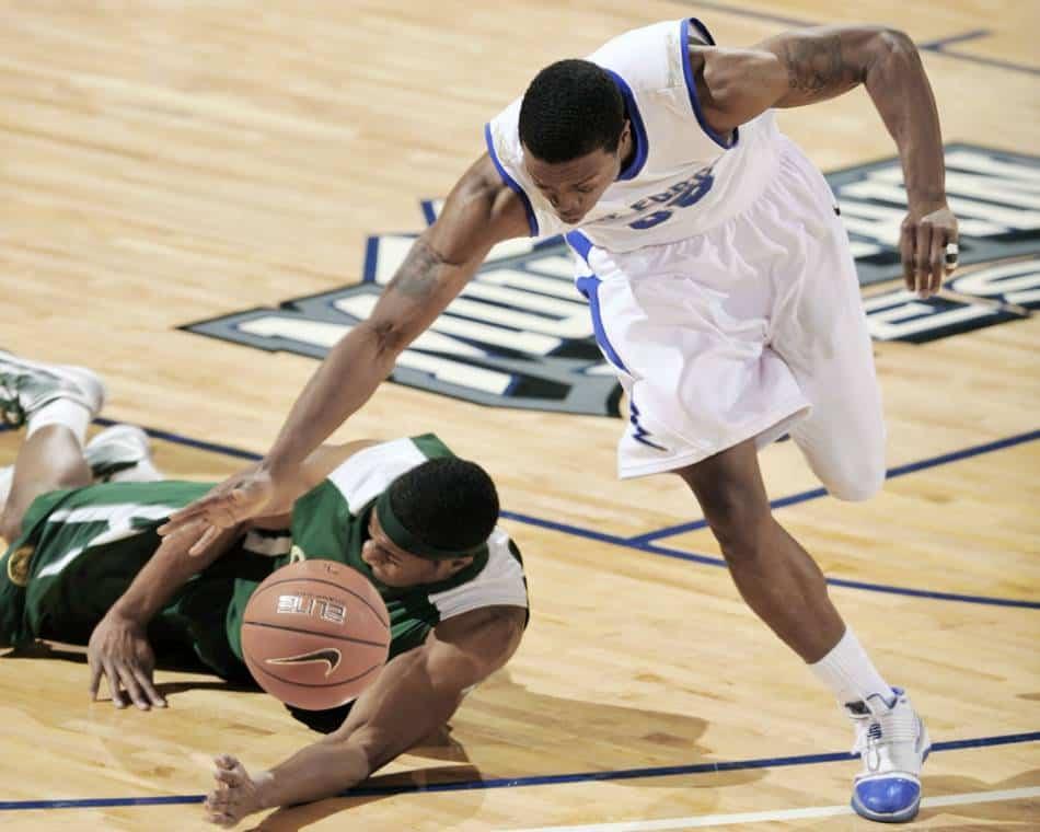 Basketball player dribbles past defender.