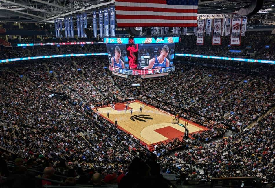 Stadium full of fans look on during NBA game.