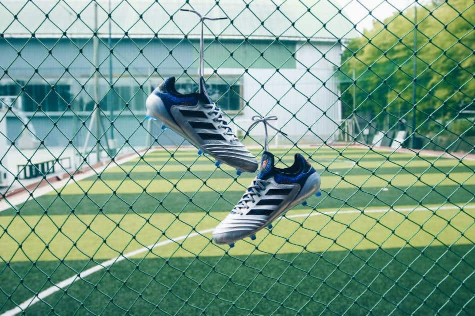 Soccer cleats hanging from fence.