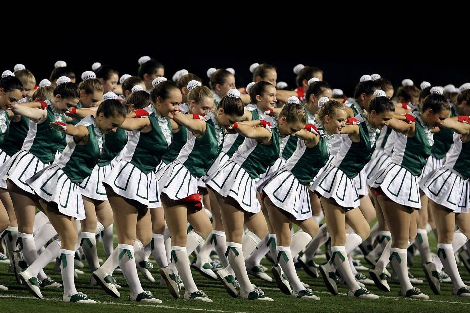 Group of girls dancing on a football field.