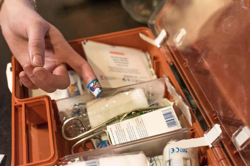 Man going through orange first aid kit.