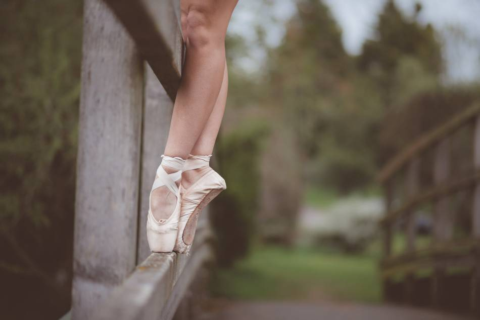 Girl standing on the rail of a bridge in ballet shoes.