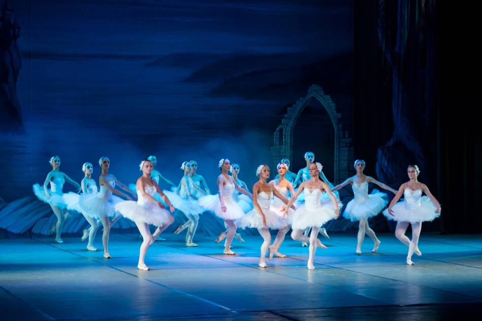 Women performing a dance in tutus and white leggings.