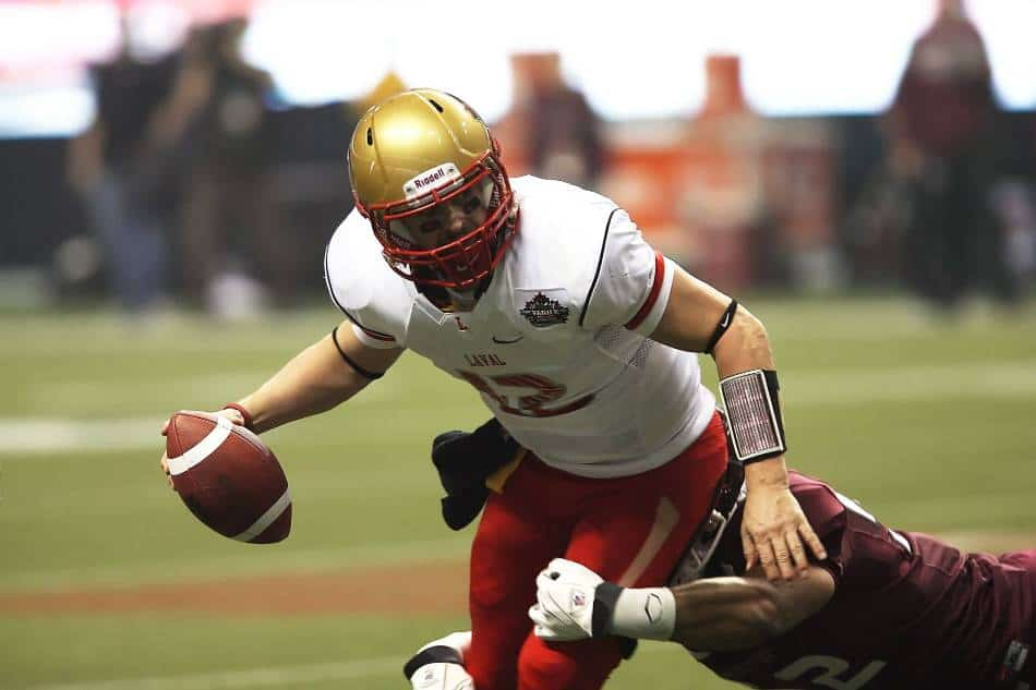 Quarterback with gold helmet gets sacked by defensive player in red.
