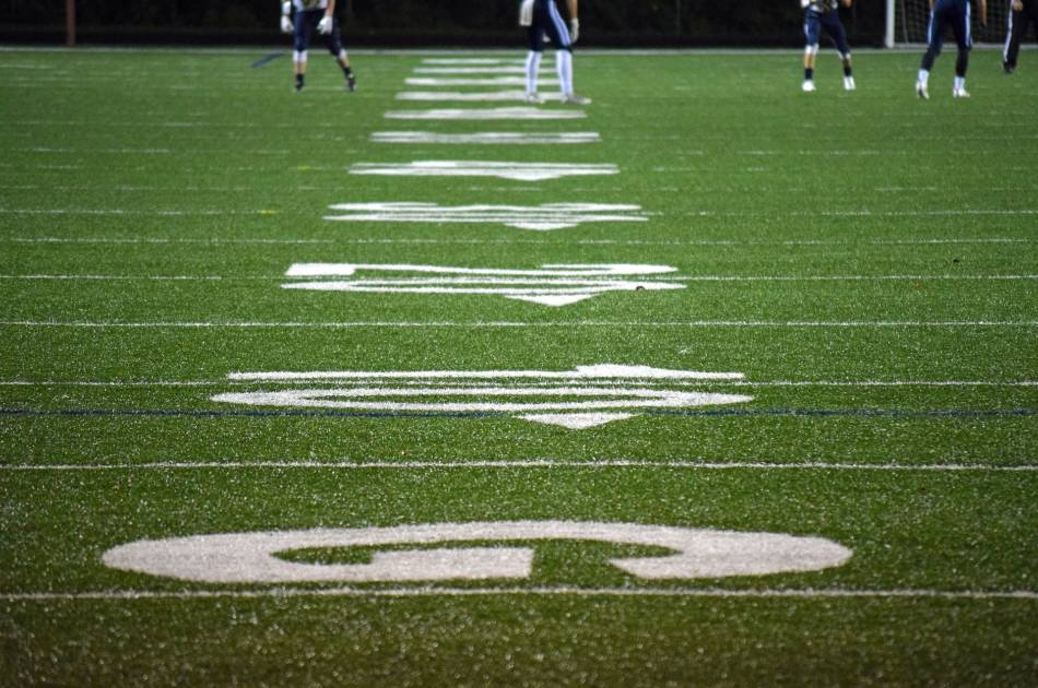 Football field yard-lines with players in background.