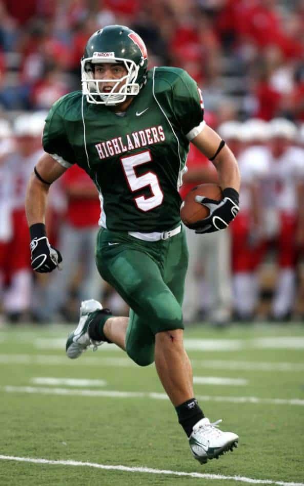 Football player protects football as he runs upfield.