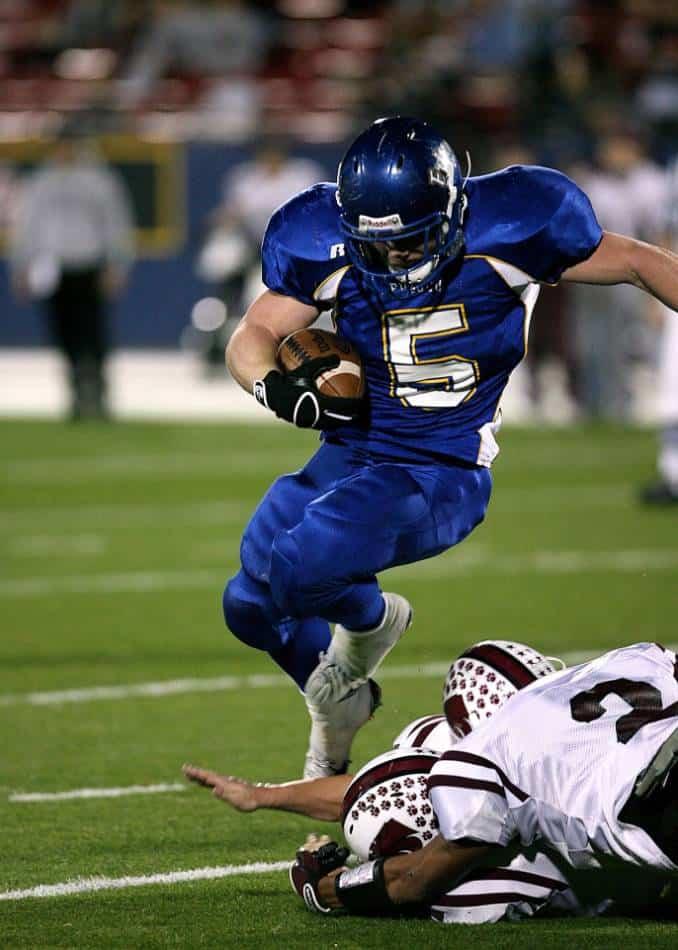 Football running back running past defenders.