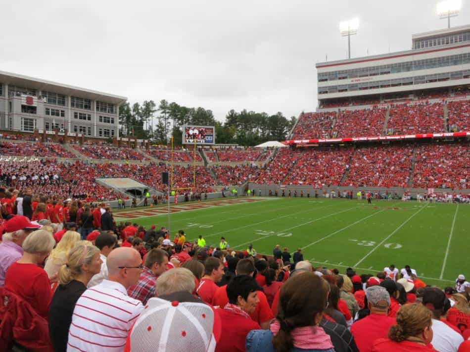Packed football stadium watching football game.