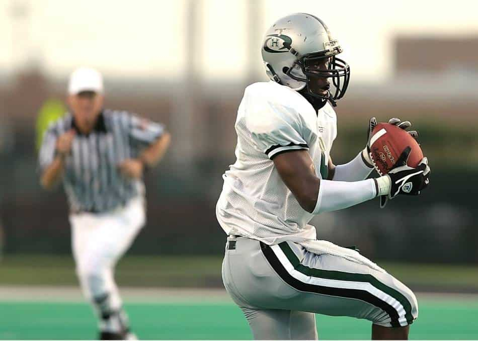 Football player catching and running with football.