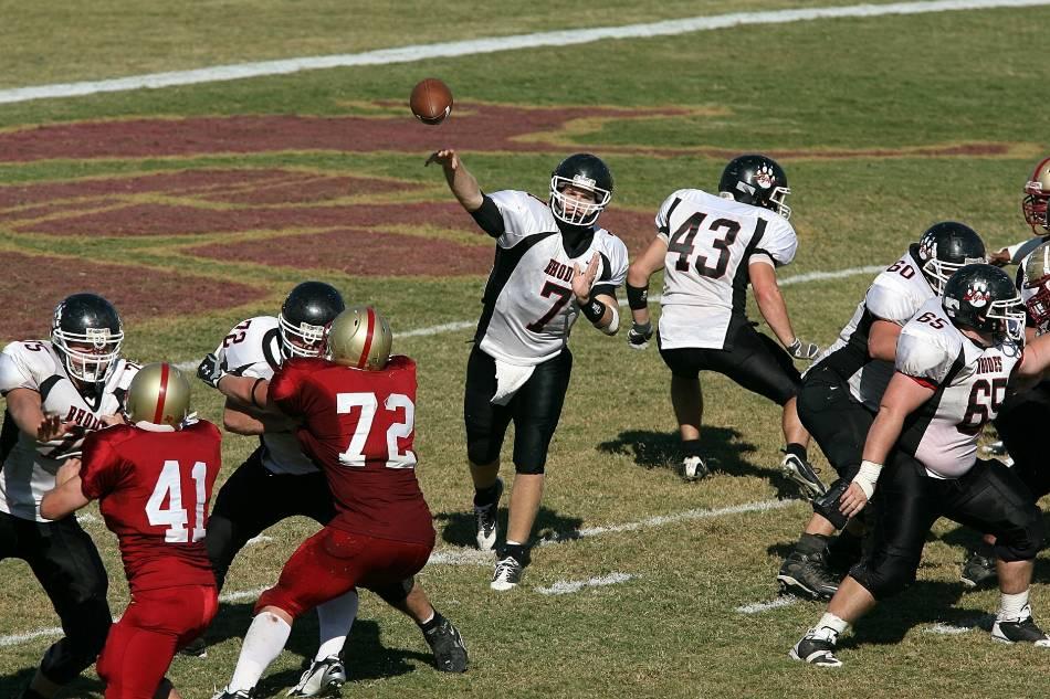 Football quarterback throws football.
