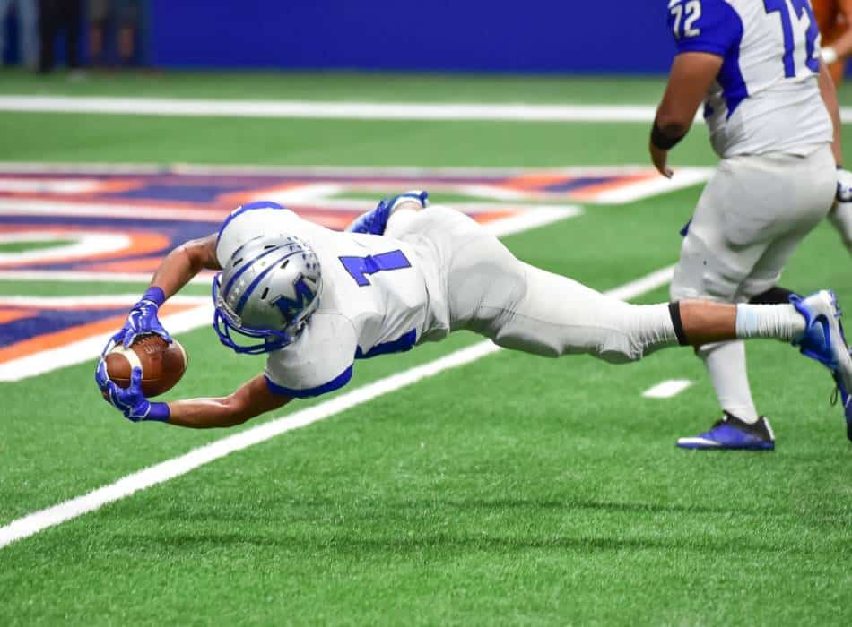 Football player dives into the end zone.