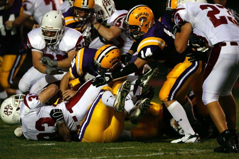 Football teams form a pile.