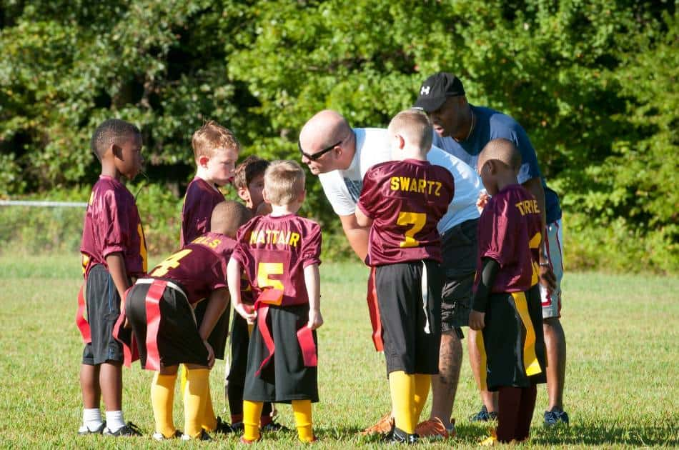 Coach bends over to talk to youth flag football team.