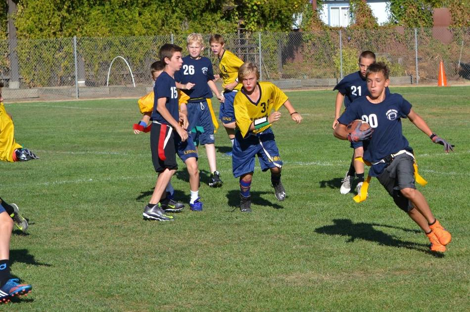 Youth flag football player runs with football as other team chases him.