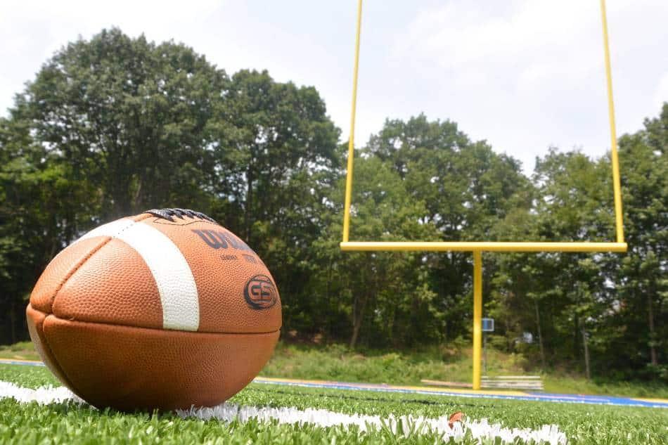Football lies on field near goal posts.