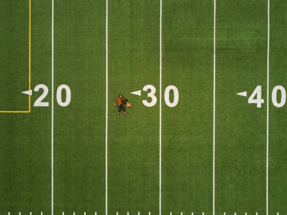Woman laying on football field.