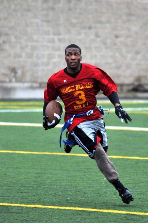 Man playing flag football runs with football.