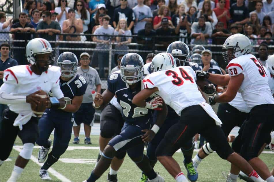 High school quarterback pursued out of hte pocket.