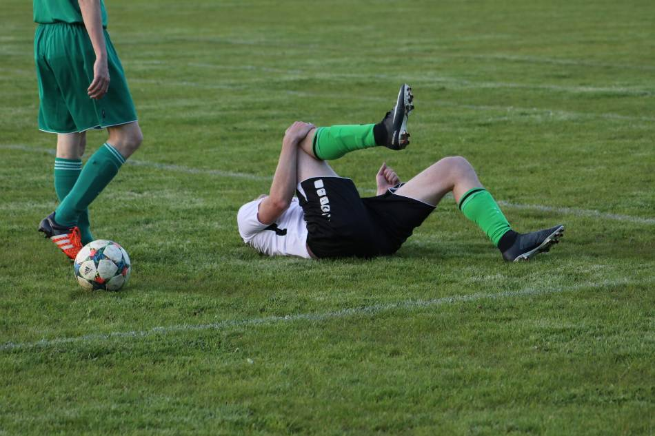 Soccer player on ground holding knee, while other player comes over.