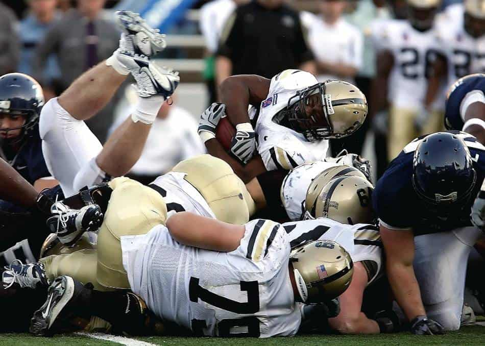 Football players pile up during play.
