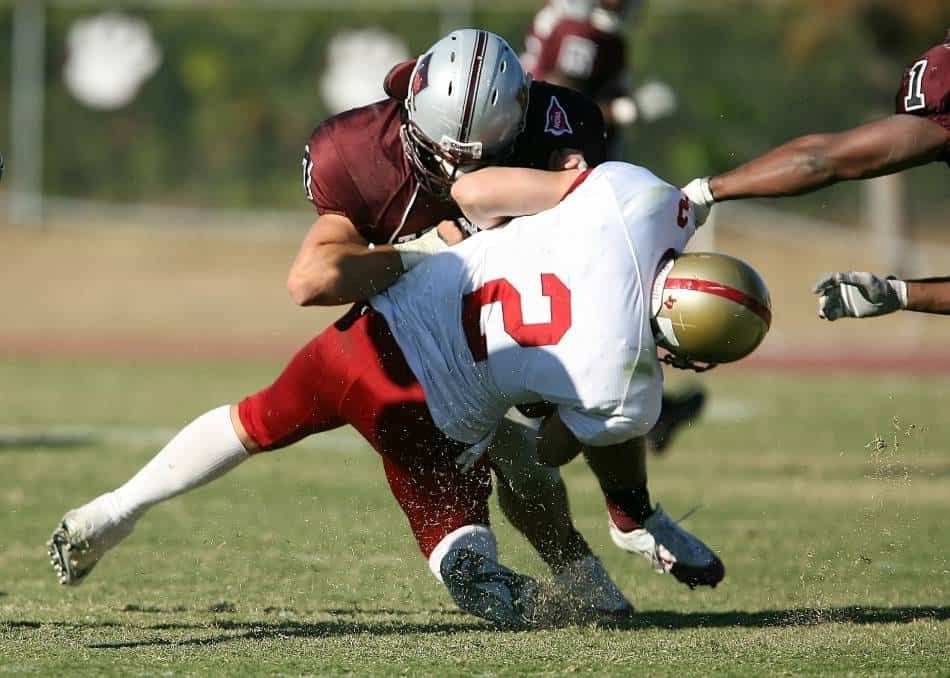 Football player on the defense tackles the player with the ball.