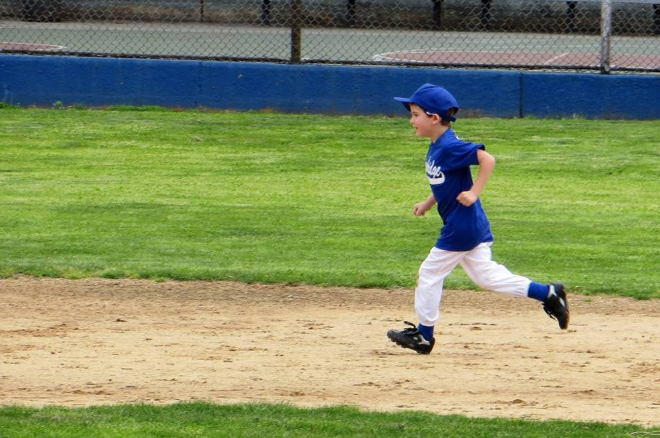 Young boy running the bases in baseball.