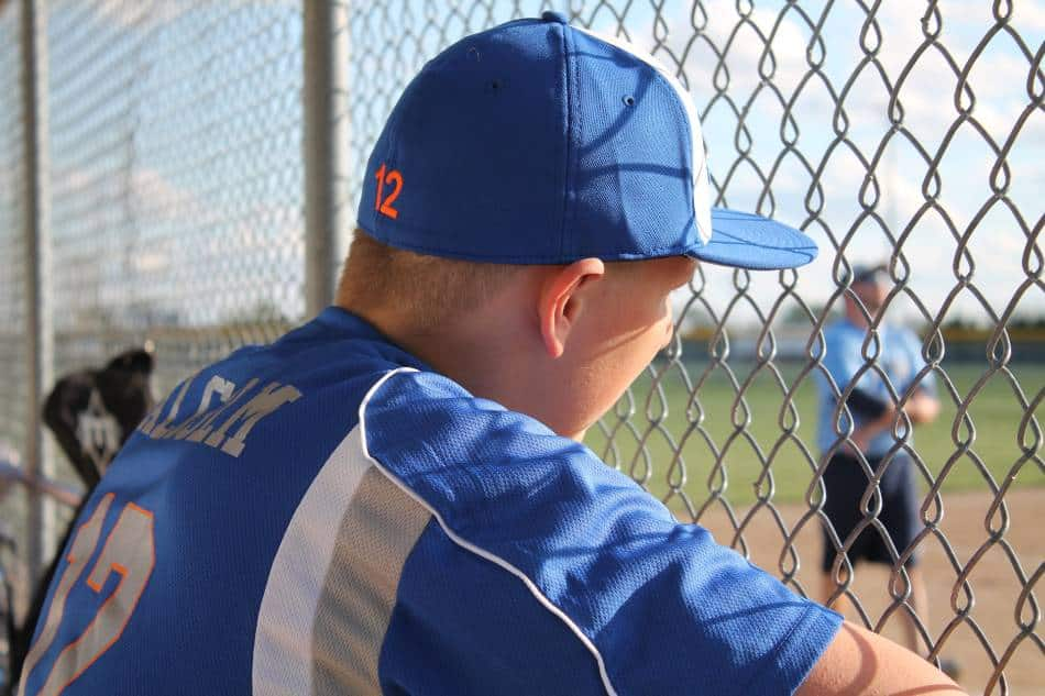 Baseball player watches game from the dugout.