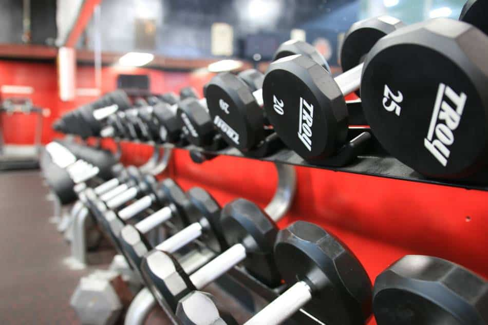 Weight rack at the gym full of dumbbells.